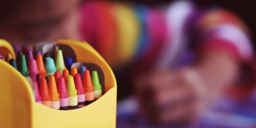 Box of crayons with blurred image of child colouring in the background