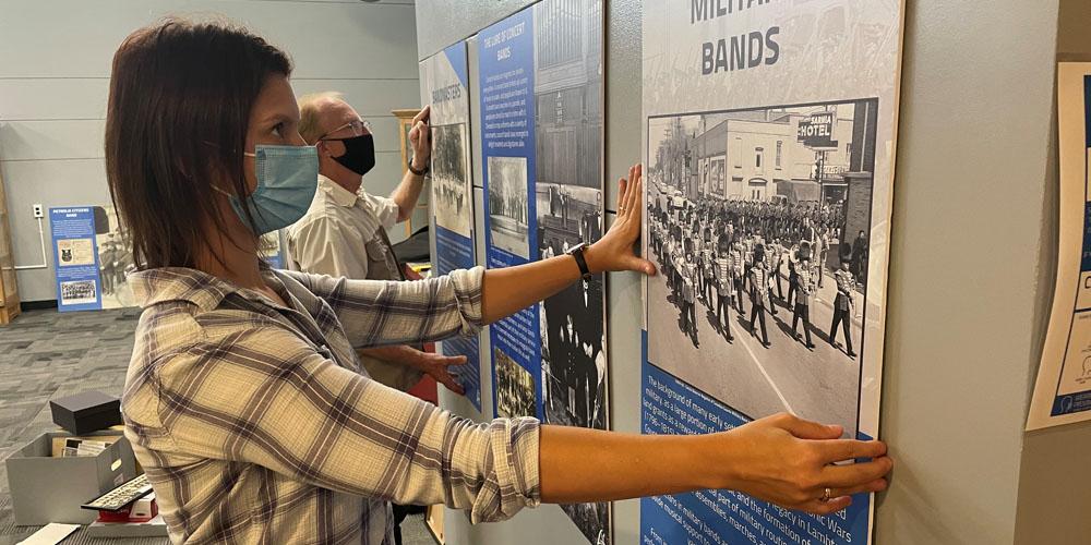 Archivist, Nicole Aszalos of Lambton County Archives installs exhibit with Don Vander Klok from the Lambton Concert Band