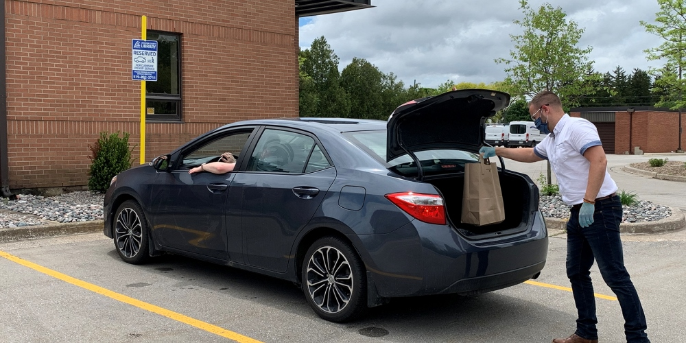 Library staff member placing materials in trunk of car waiting for curbside pickup service