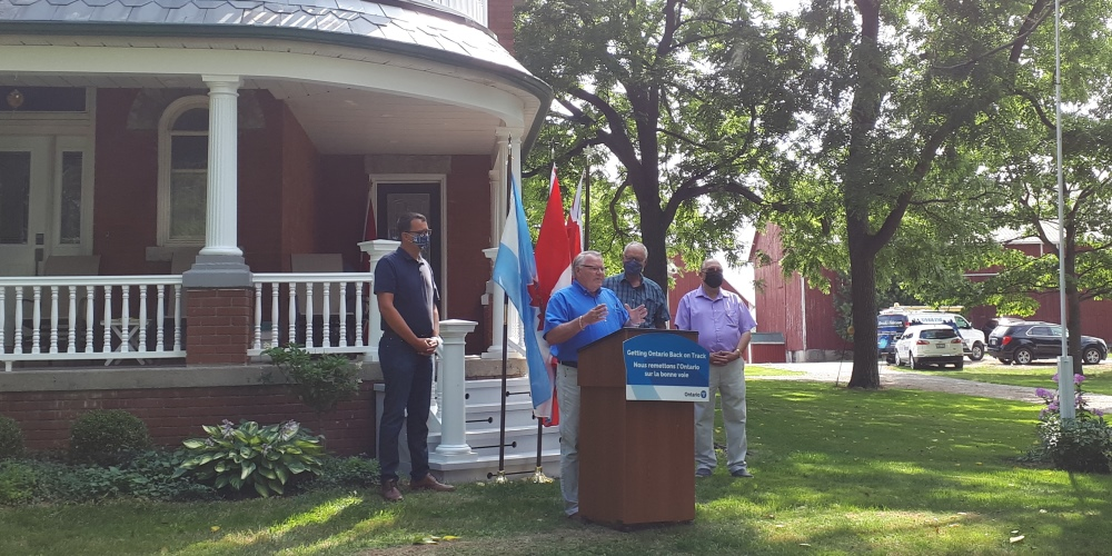 Warden Weber speaking at the SWIFT funding announcement standing in front of flags and a farmhouse.