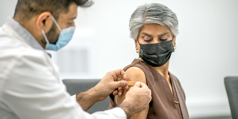 Woman has bandage placed on arm after receiving COVID-19 vaccine.