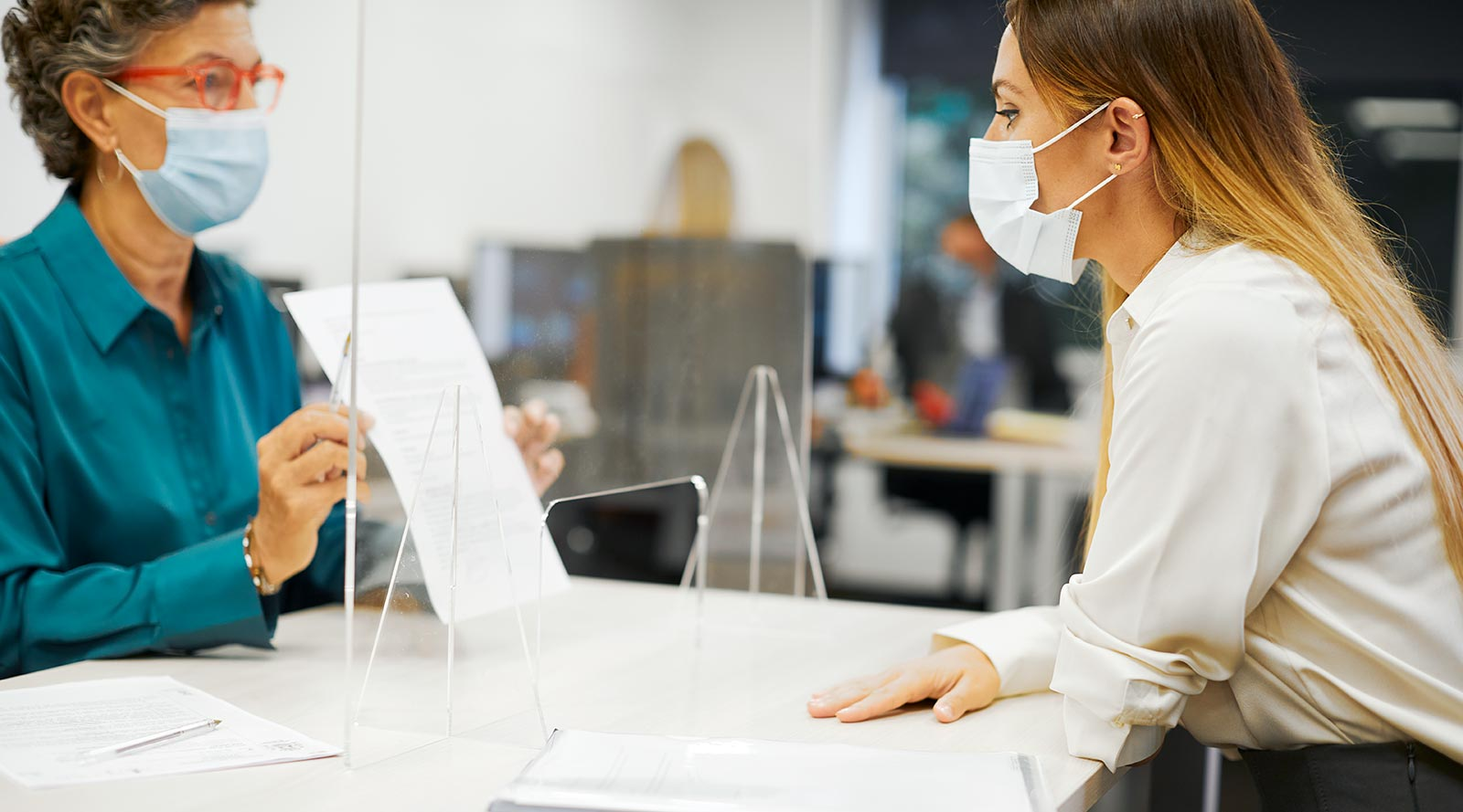 Woman checking a customer's vaccination receipt
