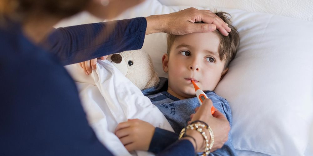 Child having temperature taken by adult