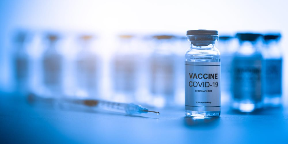 Vials of the COVID-19 vaccine with a syringe lying in front of them