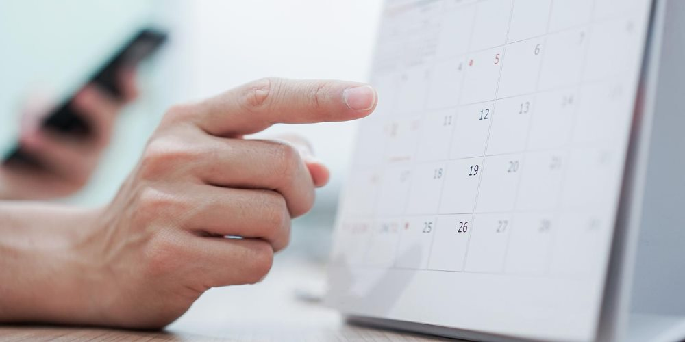 Person holding phone pointing at calendar