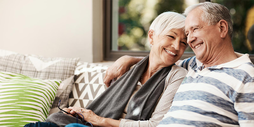 Senior man and woman sitting on couch