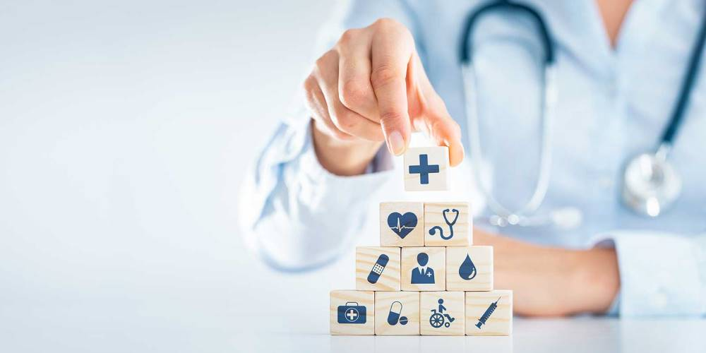 Person wearing stethoscope stacking wooden blocks with healthcare related icons on them