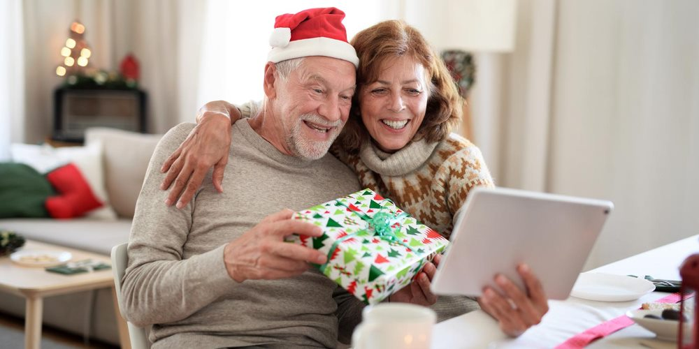 Couple holding a gift talking to someone through a tablet video call.